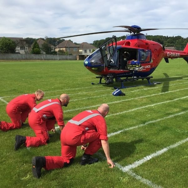 3 paramedics kneel in 'ready set go' position in front of aircraft